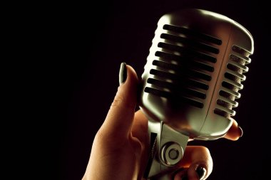 Woman singer hand with microphone in retro style against black background