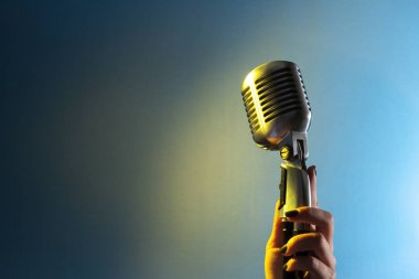 Woman singer hand with microphone in retro style