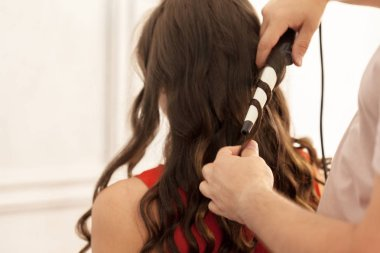 Close view of hair stylist curling hair client in hairdressing salon