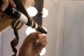 Zavřít pohled kadeřnice curling vlasy klienta v kadeřnictví