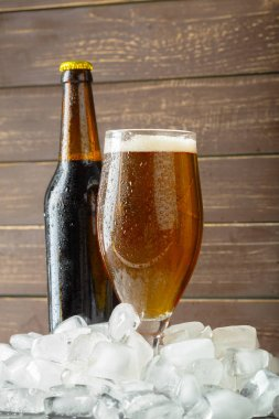 Bottle and glass with cold and fresh beer with ice cubes