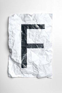 Grunge wrinkled paper letter F on white background