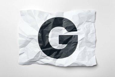 Grunge wrinkled paper letter G on white background