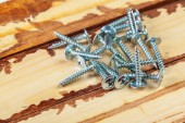 Photo close up of screws on a wooden table