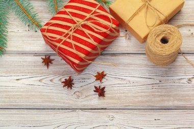 Christmas decorations, gift boxes and pine tree branches on wooden background