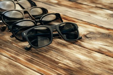 Set of dark sunglasses on brown wooden surface