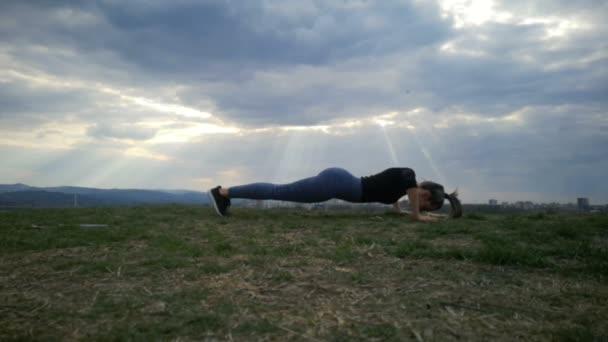 Slow Motion Woman doing Push ups, ups stampa esercizio giovane donna. Esercitandosi alla sagoma del parco. Giovane donna adatta facendo allenamento allenamento Slow Motion.