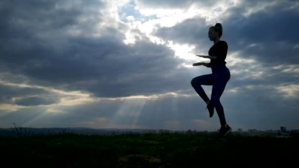 Rallentatore giovane donna che si esercita alla sagoma del parco. Giovane donna adatta facendo allenamento con movimento lento. Giovane donna felice che allunga al parco dopo un allenamento in esecuzione. Concetto di esercizio allaperto.