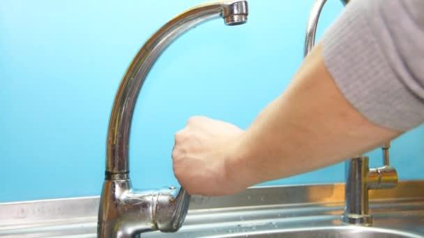 mužská ruka myje s proudem vody