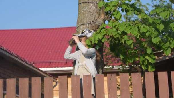 the child sitting on the fence looking through binoculars