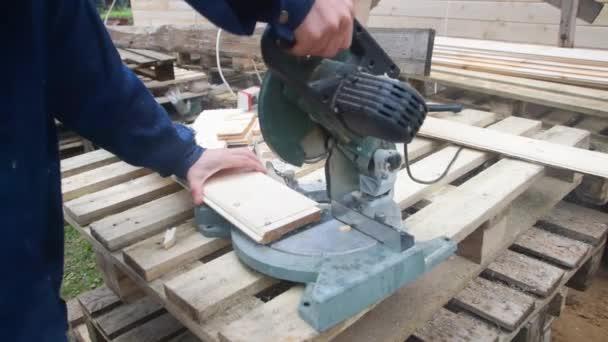 der Tischler, der mit der elektrischen Säge auf Holz arbeitet