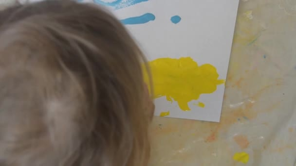 the child draws with paints and brush sitting on the floor