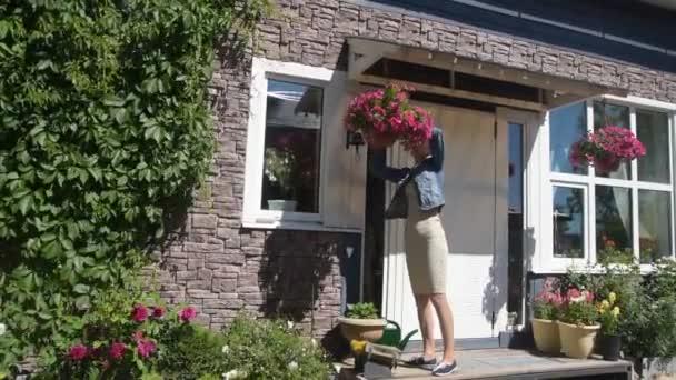a lány Kertész metszés virágok a bejáratnál a ház
