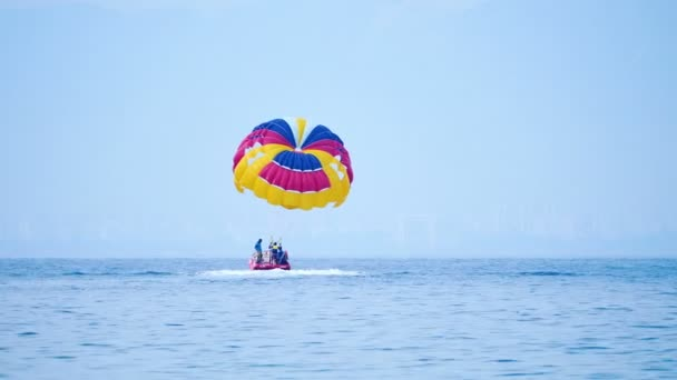 KEMER, TURKEY - May 12, Tourists have fun in the water attraction - parasailing. Man with parachute moves with motor boat.