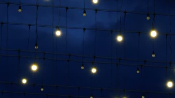 Venkovní světlo žárovky se houpat na dráty z větru. Moskva zdobené pro nový rok a Vánoce oslava. Rusko.