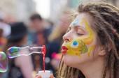 Moskva, Rusko - 22. dubna 2012: Portrét mladé ženy s dredy foukání mýdlové bubliny na flashmob na Arbatu v Moskvě