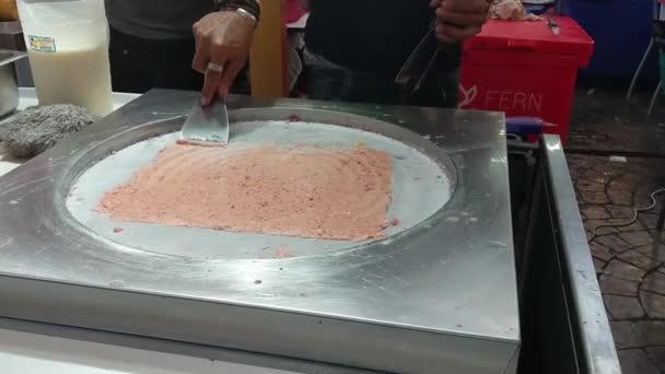 Příprava smažené zmrzliny smaží jahodové závitky na ledové pánvi. Válcovaná zmrzlina, ručně vyrobený zmrzlinový dezert
