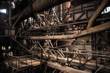 Old factory with sun beams. Horizontal industrial retro photography.Old factory horizontal photography. Metal planks and pipes. Dark industrial interior of large  hall for manufacturing or warehousing.
