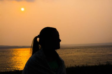 Beautiful woman portrait at sunset. silhouette of young girl. female walking in plaid against summer beach.