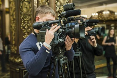 Operator with professional video camcorder on room background.