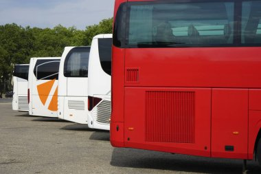 many tourist buses standing on the street in perspective. summer time season.