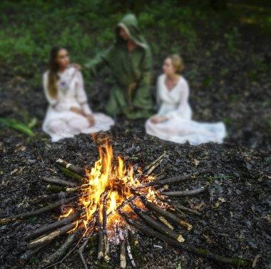 Karanlık ormandaki ateşe bakan iki güzel cadı. Sihirbaz. ateşe odaklanın