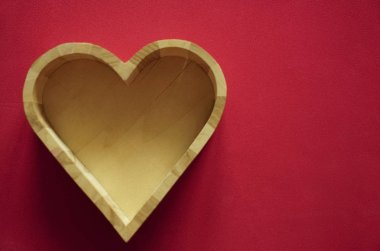 wooden box in the form of heart  on red background. empty copy space for inscription.