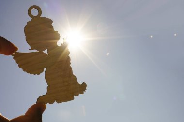 male hand holding  wooden figure of angel against sunset sky
