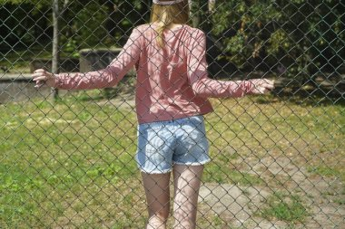 girl behind the fence.  back, rear view.