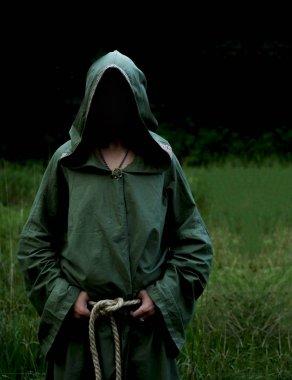 shaman man wearing  green shroud against evening forest