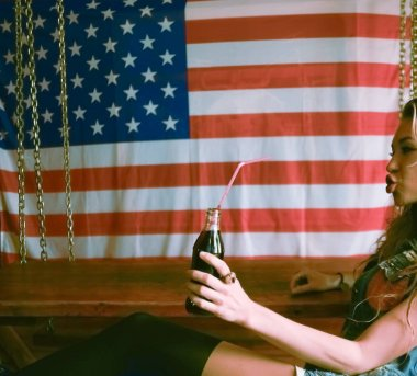 Stylish young  woman drinking  cola from full glass bottle with plastic straw