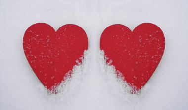 Red wooden hearts on  white  snow stock vector