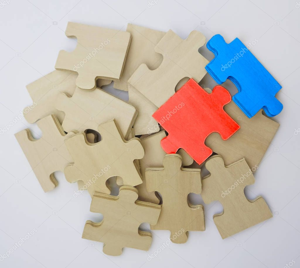 bunch of wooden puzzle pieces  isolated on white  background. one red and one blue pieces.