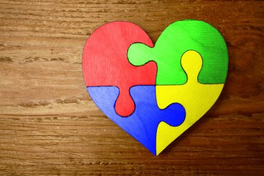heart shape from  puzzle pieces on wooden background