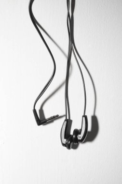 couple of  mini earbuds  hanging on white textured background. empty copy space for inscription