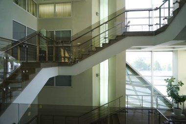 stone Stairs in modern interior. glass railings. Low Angle View Of Stairs Leading Towards modern building.