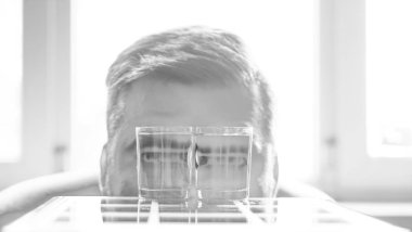 man with two glasses.  eyes magnified in the glasses filled with water.
