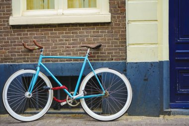 sporty old style blue bicycle on brown and white wall background. blue and brown bicycle parked  exterior. red brick wall background