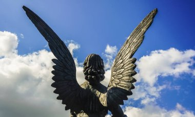 Sculpture of a wing angel on blue sky background. back view.