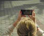 Junge Frau besucht Urlaubsort mit Smartphone zum Fotografieren im Freien.