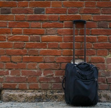 Packed suitcases on red  brick wall background. empty copy space for inscription.