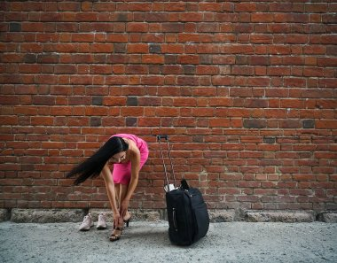 Woman with suitcase near red brick wall. Travel concept. Girl standing with a big case near fence. Free space for inscription. dressing up with high heels in sneakers