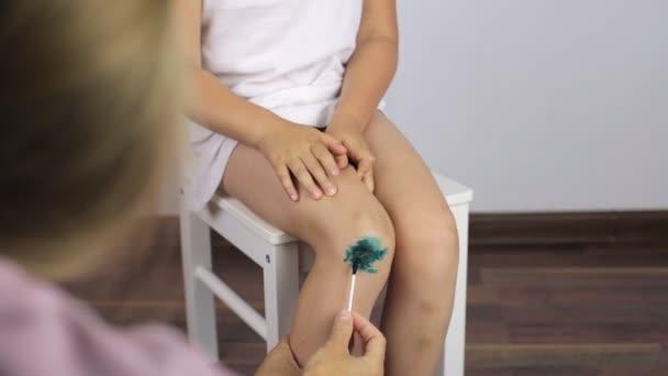Maminka pracuje v oblasti kolena dívky