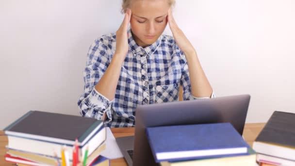 Dívka masáže hlavy při práci na notebooku