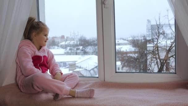 Dívka sedí a dívá z okna smutně