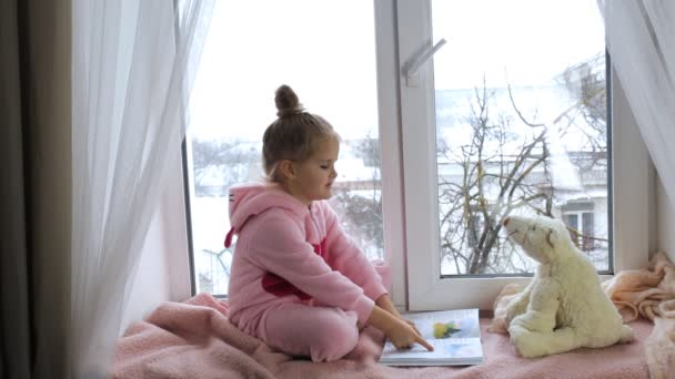 Girl sits on the windowsill and reads