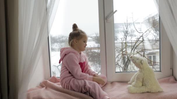Mädchen sitzt mit Spielzeug auf der Fensterbank