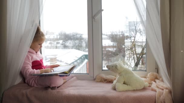 Malá holka sedí na parapetu a čtení