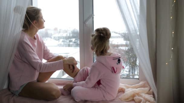 Máma a dcera sedí na okenním parapetu