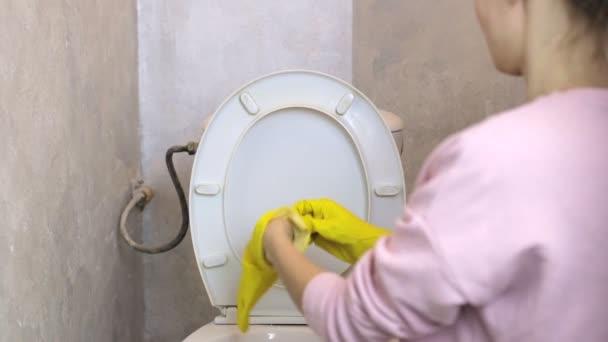 Žena s žluté gumové rukavice čistí záchod